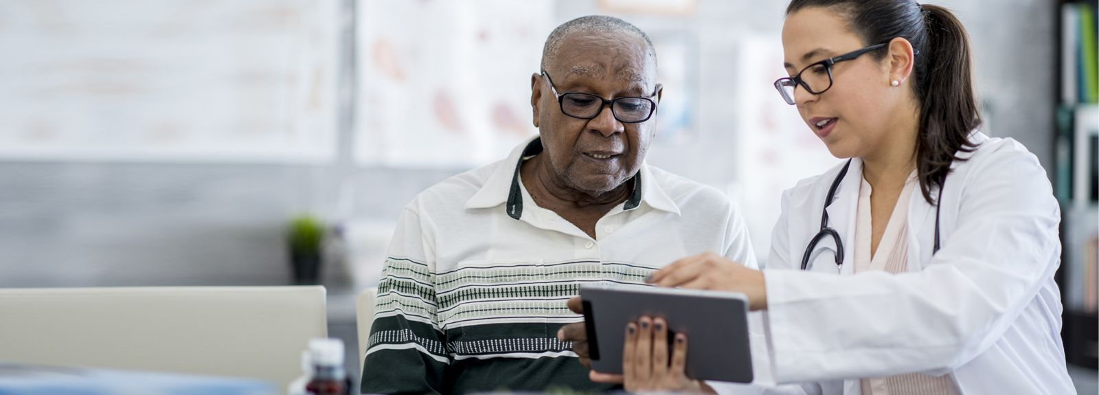 Doctor and senior patient looking at tablet
