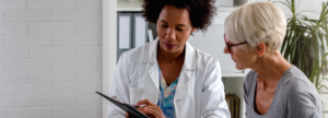 Health professional showing a person something on a tablet