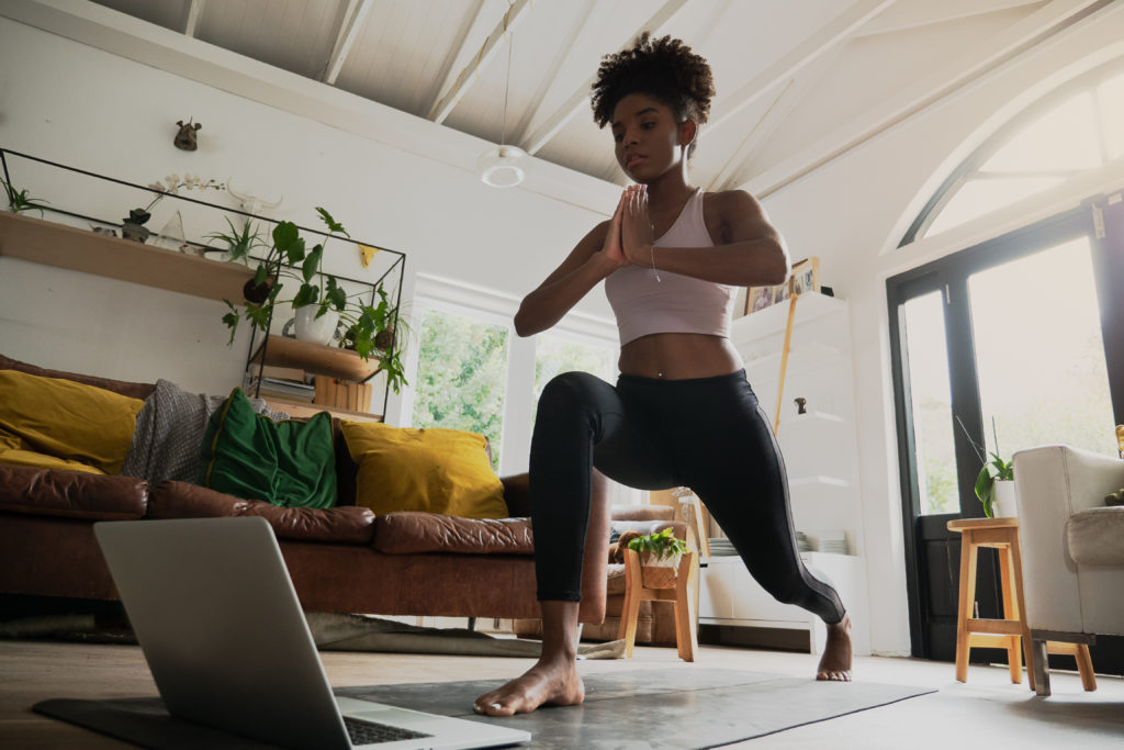Wide angle shot of young mixed race female doing home workout or yoga from home, following an online workout on computer or online.