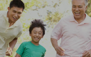 Older man, man and young boy laughing