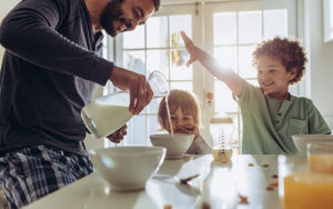 Man pouring milk into bowl of cereal with kids